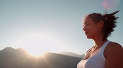 4K beautiful girl in white clothes doing yoga in the mountains,sunrise,sun glare Stock Footage