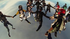 Many skydivers make formation in blue sky. Extreme. Open parachute. Stunts Stock Footage