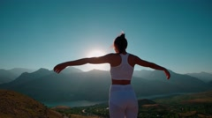 Young cheerful woman raising hands on beautiful mountain top above the Golden Stock Footage