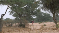 African savanna landscape - walking woman and children in the background Stock Footage