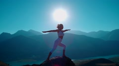 4K yoga in the mountains,the sunrise, beautiful girl in white clothes doing yoga Stock Footage