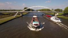 Two cargo vessels passing underneath white steel bridge, aerial Stock Footage