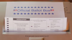 Voting ballot fed into paper shredder that is labeled as the Official Ballot Box Stock Footage
