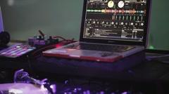 Dj spinning at turntable on party in nightclub. Laptop. Purple spotlights Stock Footage