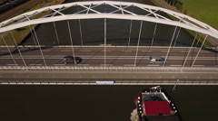 Steel bridge over river with traffic and vessel, aerial. Stock Footage