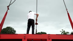 A worker standing on a metal structure suspended by crane. Stock Footage