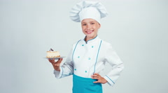 Portrait young baker holds piece of cheesecake and gives you it Stock Footage