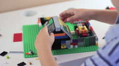 Child's hands playing with a construction toy set Stock Footage