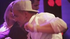 Dj spinning at turntable on party in nightclub. Girl dance. Purple spotlights Stock Footage