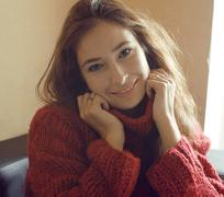 Young pretty real woman in red sweater and scarf all over her face smiling at Stock Photos