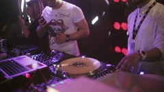 Dj spinning at turntable on party in nightclub. Spotlights. Mc girl and boy Stock Footage