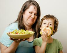 Mature woman holding salad and little cute boy with hamburger teasing close up Stock Photos