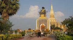 Man prays at statue King Setthathirat, That Luang,Vientiane,Laos Stock Footage