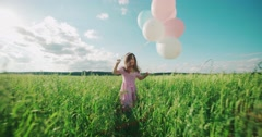Little Asian girl in a dress running through green wheat field with balloons. Stock Footage