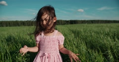 Little Asian girl standing in a green field of young wheat, flowing hair,slow Stock Footage