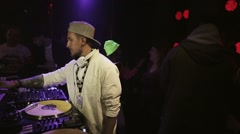 Dj spinning at turntable on party in nightclub. Spotlights. People. Cheering Stock Footage