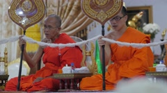 Young and older monk praying in temple,Vientiane,Laos Stock Footage