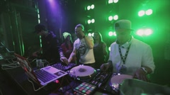 Dj spinning at turntable on party in nightclub. People dancing. Green spotlights Stock Footage