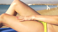 Beautiful model applies a sunscreen for a legs. HD Stock Footage