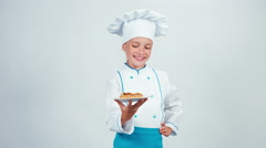 Young baker holds plate with little cake with nuts and gives you it Stock Footage