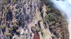 POV from a water dropping helicopter flying over a fire. Stock Footage
