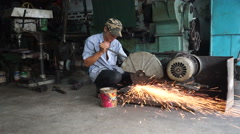 Asian man is cutting a metal abrasive with grinder in his repair shop at Stock Footage