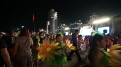 Young participants of a festival in bright carnival costumes with flowers go Stock Footage