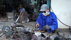 Asian worker in blue uniform, sunglasses and mask works with gas welding into Stock Footage