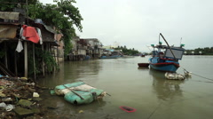 Small fishing boat is floating on the river bank in slums of vietnamese village Stock Footage