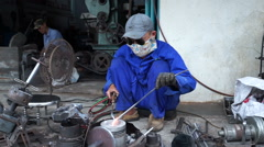 Asian man in blue uniform, sunglasses and mask works with gas welding into Stock Footage