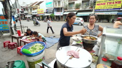 Asian woman imposes dish into a plate in snackbar on the vietnamese street at Stock Footage