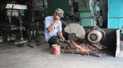 Asian man is cutting a metal with grinder in his repair shop at vietnamese city. Stock Footage