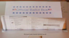Multiple ballots are put into a paper shredder labeled as an Official Ballot Box Stock Footage