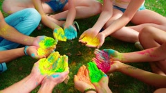 Multinational group of young people holding a lot of colored paint Holi Stock Footage