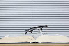 Pair of eye glasses on a worn open text book Stock Photos