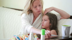 Mother treats a sick child. Mom helping a little girl to recover. thermometer Stock Footage