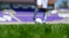 Low angle view of a footballer leading the ball on a football field Stock Footage