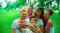 Cheerful company of young friends having fun in the Park with the colors of Holi Stock Footage