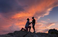 Silhouettes of a man making marriage proposal to his girlfriend Stock Photos