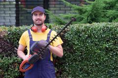 Gardener using an hedge clipper in the garden Stock Photos