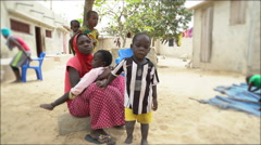 Young African girl with her children - Poor African village, Senegal Stock Footage