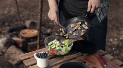 Man Folds Fried Mushrooms in Salad. Camping, Nature Stock Footage