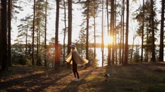 Woman in a Poncho to Turn, Have Fun in the Woods by the Lake at Sunset Stock Footage
