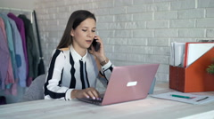 Businesswoman talking on cellphone and reading documents in office Stock Footage