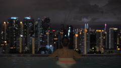 Couple looking at night Kuala Lumpur from rooftop pool, Malaysia Stock Footage