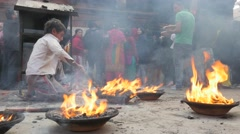 Boy poking fire at temple complex,Patan,Nepal Stock Footage