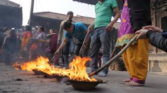 Devotees poking ritual fire at hindu temple,Patan,Nepal Stock Footage