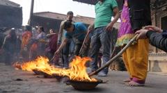 Devotees poking ritual fire at hindu temple,Patan,Nepal Stock Footage