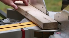 Close-up of a person using a compound-mitre saw to cut a 2 x 4 piece of lumbe Stock Footage