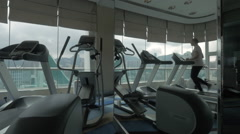 Woman exercising on running machine in front of panoramic window Stock Footage